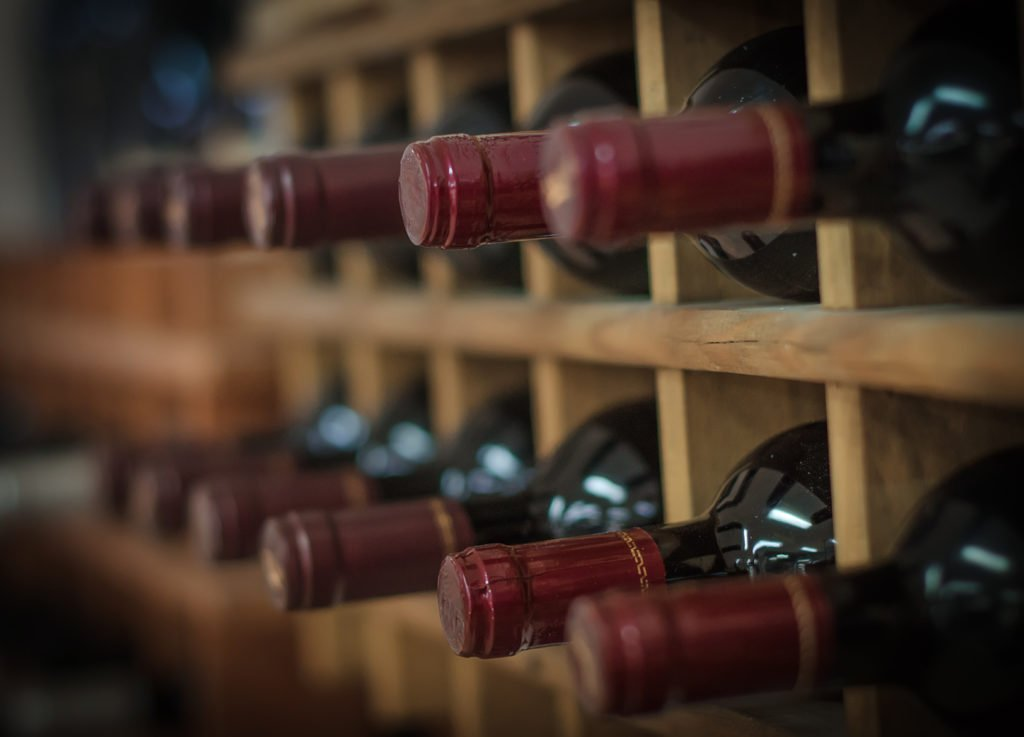 red wine bottle stacked on wooden racks
