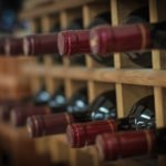 red wine bottle stacked on wooden racks