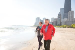 Two joggers along take a path along Lake Michigan in Chicago.
